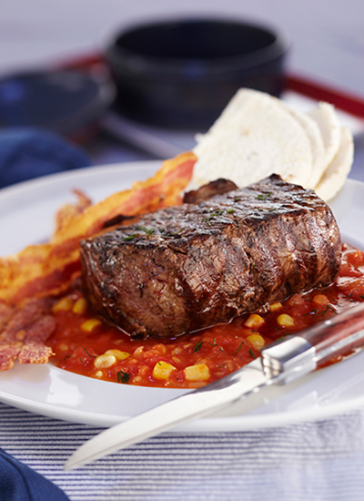 Bistec con salsa de tomate, maíz y tocineta