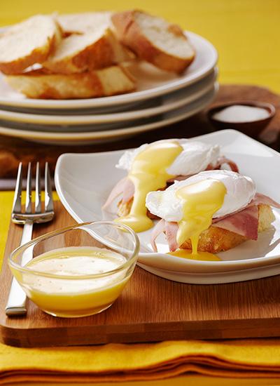 Huevos pochados sobre tostadas con jamón y salsa holandesa