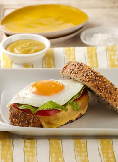 Sándwich de huevo frito, mostaza, queso holandés, pesto de albahaca y rodajas de tomate en pan de centeno y ajonjolí