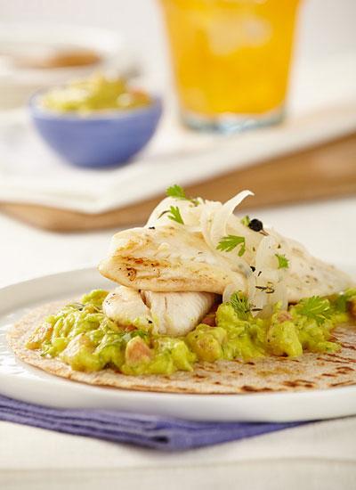 Tilapia sobre tortillinas con guacamole y cebolla en escabeche